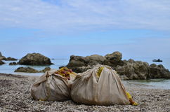 Fishing nets on the beach. Two fishing nets in cloth sacks laying on the beach of Agios NIkitas village, Lefkada, Greece royalty free stock images