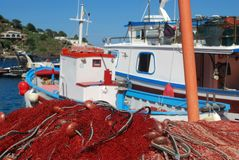 Fishing nets and fishing boats on the quay. A Mediterranean glimpse showing a pile of red fishing nets and some fishing boats on the quay Royalty Free Stock Photo
