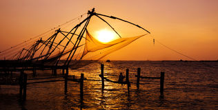 Fishing Nets of Cochin at Sunset. Indian man fishing under the great Chinese nets at Cochin, Kerela, India stock photos