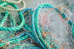 Fishing Nets and Debris. A tangled mess of fishing nets plastic rope and other debris washed up on a coastal beach ideal for an ecological hazard or pollution stock photos