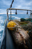 Fishing nets are on the deck of a small fishing ship Stock Photos