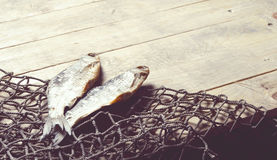 Fishing nets and dried fish still-life on the wooden background. Stock Photography