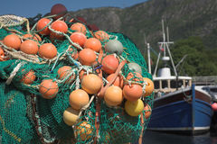 Fishing nets  and fishing boat. Fishing nets with bright orange floats in a dock; fishing boat in the background; background not in focus Stock Photos