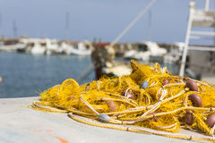 Fishing nets and Greek fishing boats mooring in port in sunrise Royalty Free Stock Photos