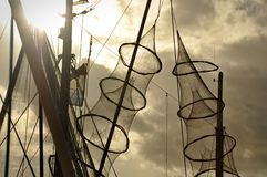 Fishing nets hanged on the mast of a fishing boat. Two fyke nets are hangedx on the mast of a fishing boat under the afternoon sun and cloudy sky Stock Image