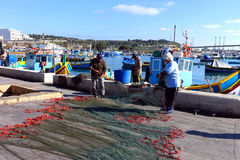 Fishing Nets In Marsaxlokk Malta. Fishermen pulling their nets in on the colorful dock of Marsaxlokk, a sheltered fishing village located on the east coast of Stock Photo