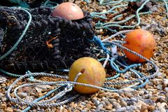 Fishing nets. Old fishing nets and boats on a shingle beach royalty free stock photo