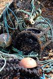 Fishing nets. Old fishing nets and boats on a shingle beach royalty free stock images