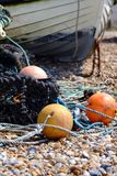 Fishing nets. Old fishing nets and boats on a shingle beach royalty free stock image