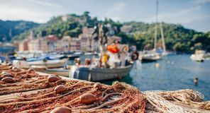Fishing nets with poplivki in the background of boats and the village of Portofino.  stock image