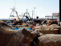 Fishing nets in the port. Fishing nets in Javea port with fishing boat in the background Royalty Free Stock Image