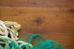 Fishing nets and ropes on wooden background. Nets and ropes on wooden background Royalty Free Stock Image