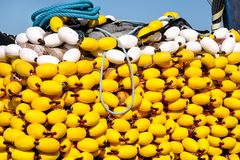 Fishing nets with yellow floats on the pile, close up. Yellow floats on the pile, covering fishing nets on the blue boat in the summer sun, close up. Fishing Stock Images