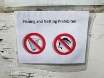 Fishing and netting prohibited sign on paper and wall. Fishing and netting prohibited sign on paper and wood wall stock photo