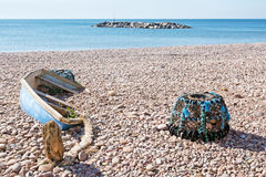 Fishing no more. Old small boat and lobster pot,abandoned. Stock Photos