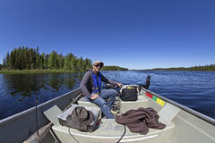 Fishing in northern Canada. Happy man fishing on a lake with a boat Royalty Free Stock Photo