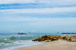 Fishing on an ocean beach shoreline Stock Photography