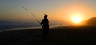 Fishing in ocean surf at sunset - South Africa Royalty Free Stock Image