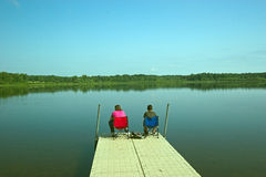 Fishing off the dock. Mother and son fishing off the dock on a pond Stock Photos