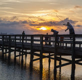 Fishing off pier at Melbourne, Florida. Men fishing off pier in Melbourne, Florida at sunset Royalty Free Stock Images