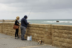 Old man fishing, with audience. Fishing old man and his audience: a passerby woman and the cat - waiting for it's share from the capture. On a cloudy day of Royalty Free Stock Image