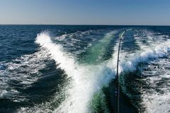 Fishing at open sea. Water wake behind a speedboat, fishing rod  with the line, clear horizon, clear horizon Stock Photo