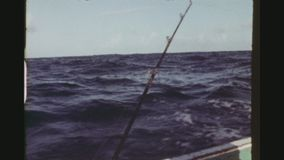 Fishing in the open sea. Republic Of Trinidad, Tobago, April 1976. Three shot sequence of two native fishermen in a small boat fishing and catching a tuna in the stock video