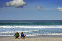 Fishing pair. A couple sit on a beach the man fishing, the woman gazing out to sea Royalty Free Stock Images