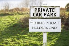 Fishing permit holders only sign post and private car park. Uk stock photos