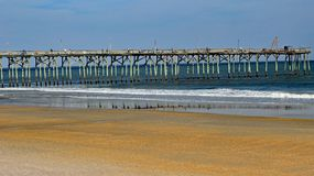 Fishing pier and beach in North Carolina. Wooden fishing pier with a low tide beach and calm seas in North Carolina Royalty Free Stock Image