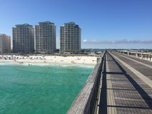 Fishing Pier with Clear Green Water. The Navarre Beach Pier located along the Florida gulf coast. Clear bright green water. Three Hotel buildings in the Stock Image