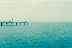 Fishing pier jutting into the blue sea. Stock Photos