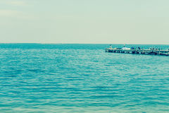 Fishing pier jutting into the blue sea. Fishing pier jutting into the blue sea and sky Royalty Free Stock Image