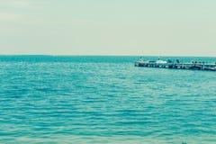 Fishing pier jutting into the blue sea. Stock Image