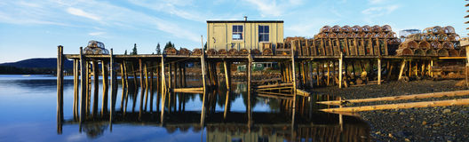 Fishing pier with lobster traps in Maine. This is a pier with a small square wooden shack. There are lobster traps stacked up on the pier. The shore is in the Stock Photo