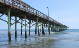 Fishing Pier. Long fishing pier going into ocean at Topsail Beach in North Carolina on beautiful hot sunny summer day stock photography
