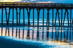 Birds in the reflections of the fishing pier. The fishing pier at Myrtle Beach SC state park with birds on the beach in the reflections Stock Photography
