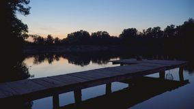 Fishing pier at night. Wooden fishing pier on pond at night stock footage