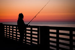 Fishing Pier. Fishing in the ocean from a pier in early morning Stock Photography