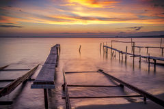Fishing pier in sea at sunset Stock Photos