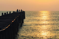 Fishing pier at sunrise. Silhouette fisherman on the old wooden bridge and sea at sunrise in rural Thailand Stock Photo