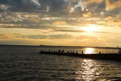 Fishing pier on the sunset. Beautiful golden sunset on Black sea in Sochi with fishermen on the pier Stock Photography
