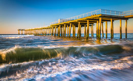 A fishing pier and waves in the Atlantic Ocean at sunrise, in Ve Stock Photos