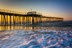 Fishing pier and waves on the Atlantic Ocean at sunrise in Ventn Stock Image