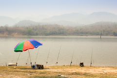 The fishing place in summer. The fishing pond, umbrella and Fishing rods Royalty Free Stock Photography