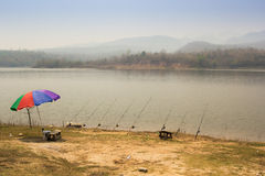 The fishing place in summer. The fishing pond, umbrella and Fishing rods Stock Photo