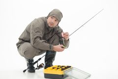 Fishing is always pleasure. Fisherman holding baits and his fishing rod in his hands sitting near the yellow box and looking in fright at something far off Royalty Free Stock Images