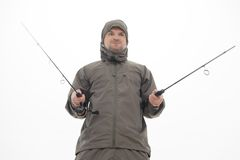 Fishing is always pleasure. Half-length portrait of excited fisherman wearing grey watertight costume and holding two spinners like two swards. Isolated on white Royalty Free Stock Image