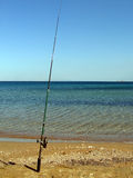 Fishing pole. On an empty beach stock photography
