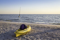 Fishing pole and canoe on the beach Stock Photos